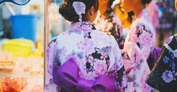 麻布十番祭りの屋台で食べ物や飲み物を楽しむ女性たち